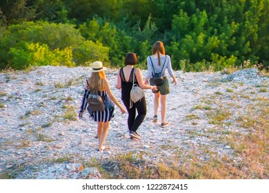 Three women in summer clothes descend from the mountain on a rocky path against the background of green forest.