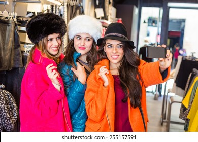 Three women taking a selfie wearing colorful coats in a clothing store. They are happy and enjoy funny clothes. Shopping concept, also related to social media addiction.