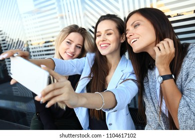 Three women taking a selfie while shopping in a clothing store. They are happy and smiling at camera. Shopping concept