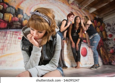 Three women talking about sad teenager sitting alone