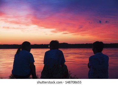 Three women are talking each other at sunset by the river