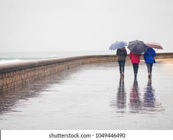 Three women under umbrellas walking near the stormy ocean in the rain