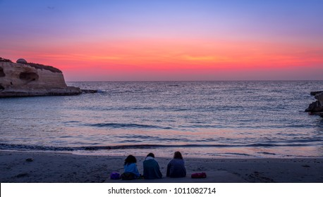 Three women waiting for the sunrise in front of the sea (Puglia region, South of Italy). Concept of frienship, travel and adventure.