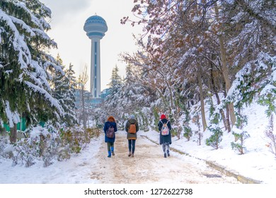 Three women walk to Atakule through botanical garden under snow, Ankara Turkey