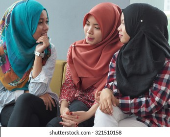 Three women wearing hijab are in a discussion.