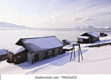 Three wooden abandoned house within the arctic snows in Grenfjord, Barentsburg, Svalbard. Beautiful snow mountain peaks on the horizon, silence and calm, background.