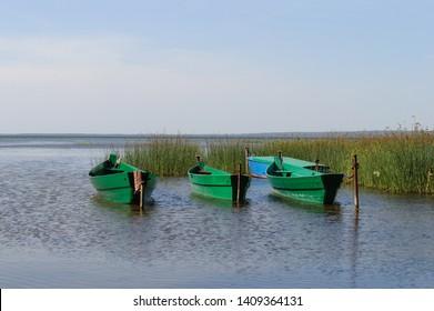 Three wooden boats on Lake Pleshcheyevo near the city of Pereslavl Zalessky, Russia
