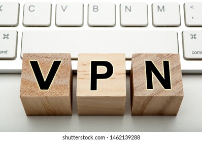 three wooden cubes with inscription VPN with the computer keyboard close up