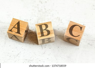 Three wooden cubes with letters ABC - stands for Always Be Closing - on white board.