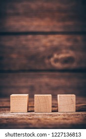 Three Wooden Cubes on Wood Background with Copyspace