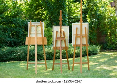 Three wooden easels with paintings standing on a green lawn in a shady garden in a concept of art and nature.
