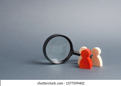 Three wooden human figure stands near a magnifying glass on a gray background. Search for vacancies and work. Human resources, management. The concept of the search for people and workers.
