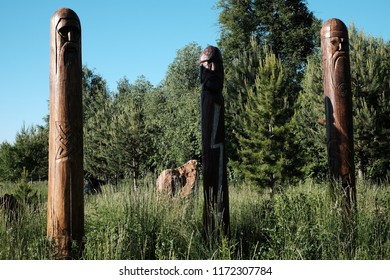 Three wooden idols of various gods of the ancient Slavs standing in the midst of tall grass. The symbols of ancient Slavs are carved on the idols. On the middle idol painted white lightning.