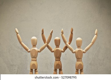 Three wooden mannequin hands up as winners