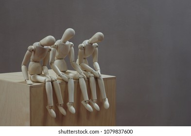 three wooden mannequins sitting close together on a wooden box rest looking downwards. Grey background. Room for text