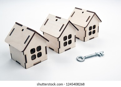 three wooden miniature houses and a door key on a white background close up