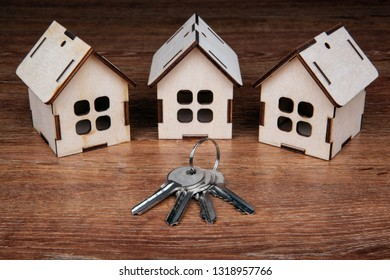 three wooden miniature houses and a door key on a wooden background close up