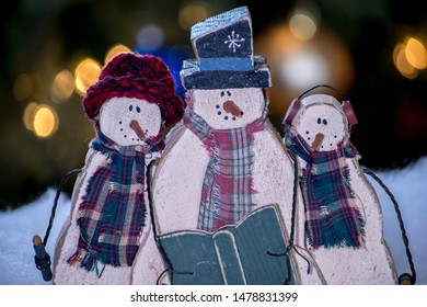 three wooden snowman pose with a song book to sing Christmas carols