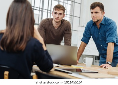 Three work colleagues in a serious discussion with a view over the shoulder of a woman to two men leaning on the table listening