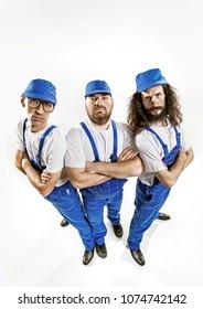 Three workers posing on empty studio background