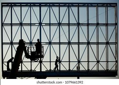 Three workers in silhouette installing the digital advertising billboard.