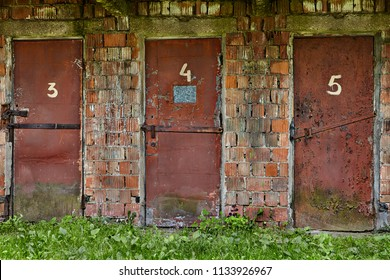 Three worn red doors, upholstered in metal, and numbered three, four, five in an abandoned warehouse in brick building.