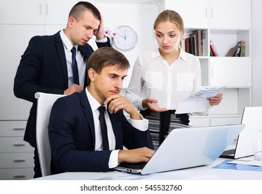 three worried coworkers different sexes experiencing business failure in firm office
