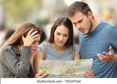 Three worried lost tourists trying to find a location in a paper map on the street