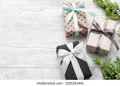 Three wrapped gift boxes & twigs on white wood background with copy space. Christmas, New Year, Boxing day concept.