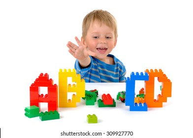 The three year child playing with letters on the table isolated on white