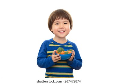 Three year old boy isolated on white background holding bowl of vegetables, carrots and broccoli. Smiling, happy, bright preschooler eating healthy snacks with a natural expression. Happy and healthy.
