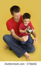 Three year old boy taking family photo with digital camera.