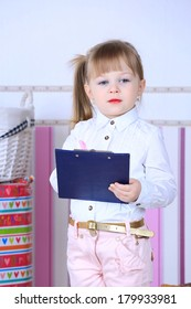 A three year old child girl in pink pants and white blouse with a hairstyle and makeup red lips holding a clipboard and a pen smiling