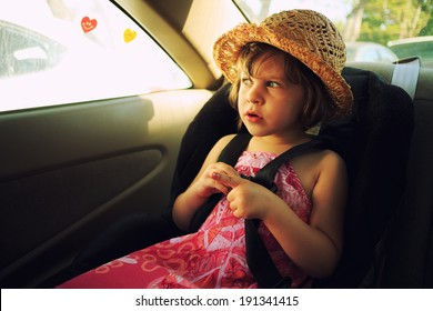 Three year old girl sitting in car seat.