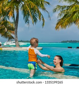 Three year old toddler boy in resort swimming pool with mother. Summer family vacation at Maldives.