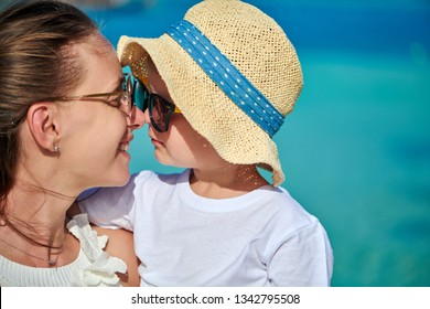 Three year old toddler boy on beach eskimo kissing his mother. Summer family vacation at Maldives.