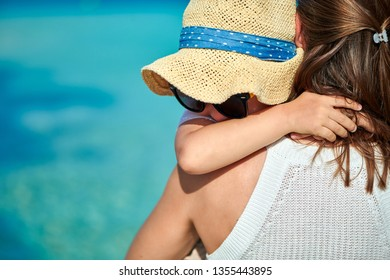 Three year old toddler boy on beach giving a hug his mother. Summer family vacation at Maldives.