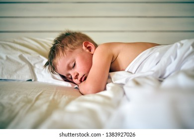Three year old toddler boy sleeping on pillow under blanket