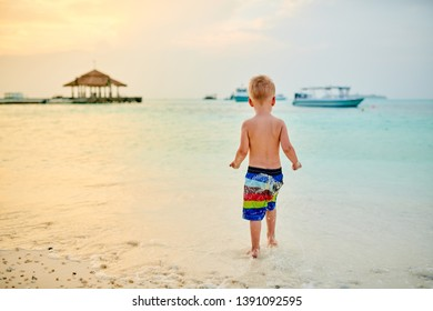 Three year old toddler boy on beach at sunset. Summer family vacation at Maldives.
