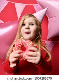 Three years girl toddler kid with pink balloons and flags hold red eat sweet donut in birthday cap celebrating