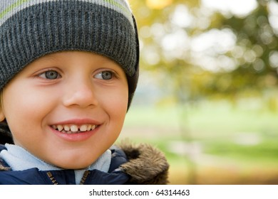 Three years old boy in cap smiling in autumn scenery