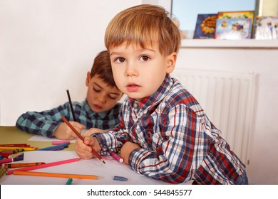 Three years old boy drawing using a pencil in kindergarden