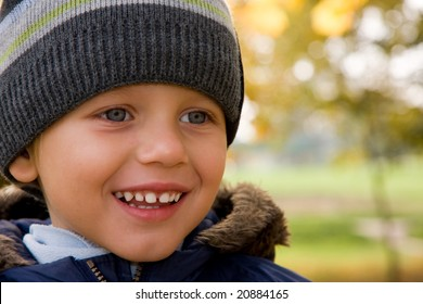 Three years old boy smiling in autumnal scenery