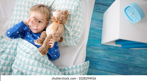 Three years old child crying in bed. Boy hiding and closing eyes with hands