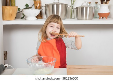 three years old child with orange and red apron making and cooking a sponge cake at kitchen home, eating yogurt with wooden spoon looking