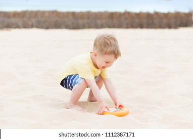 Three years old child plays frisbee on the sand on beach near sea. Beach games and active toddler kid on vacation, happy holiday concept
