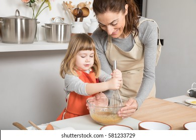 three years old child and woman, in teamwork, making and cooking a sponge cake at kitchen home, whipping cream in glass bowl with metal whisk
