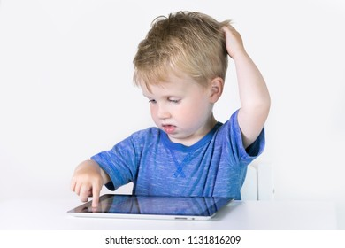 Three years old little kid boy playing children educational or developing games or on the tablet computer at home on white background