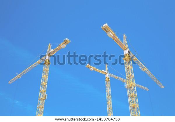 three-yellow-building-cranes-against-600