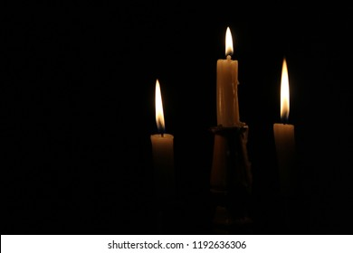 three yellow candles in the dark